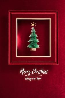 Prettige kerstdagen en gelukkig nieuwjaarstekst en kerstboom in vilten fotolijst op fluweel rood vilt