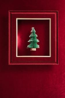 Prettige kerstdagen en gelukkig nieuwjaarstekst en kerstboom in vilten fotolijst op fluweelrood