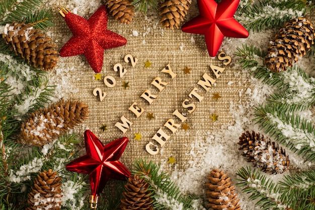 Prettige kerstdagen en nieuwjaar 2022. feestelijke achtergrond met rode sterren, besneeuwde takken van sparren en kegels op jute. bovenaanzicht.