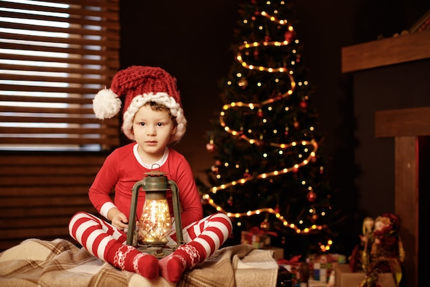 Prettige kerstdagen en prettige feestdagen een kleine jongen zit met een lantaarn bij de kerstboom nieuwjaar, elf.