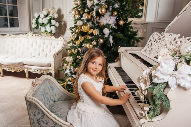 Prettige kerstdagen en prettige feestdagen. leuk meisje in het witte klassieke binnenlandse spelen op een witte piano verfraaide kerstboom. nieuwjaar