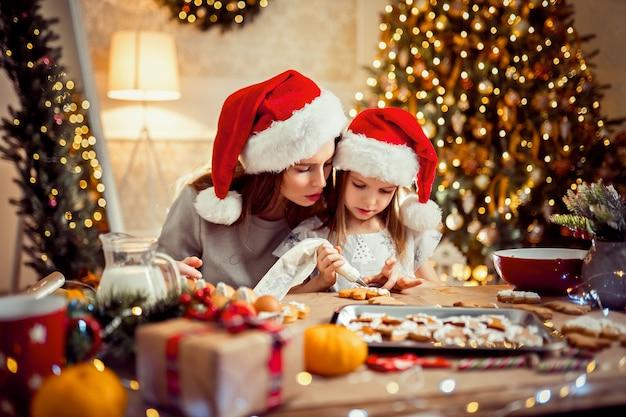 Prettige kerstdagen en prettige feestdagen. moeder en dochter kokende kerstmiskoekjes.