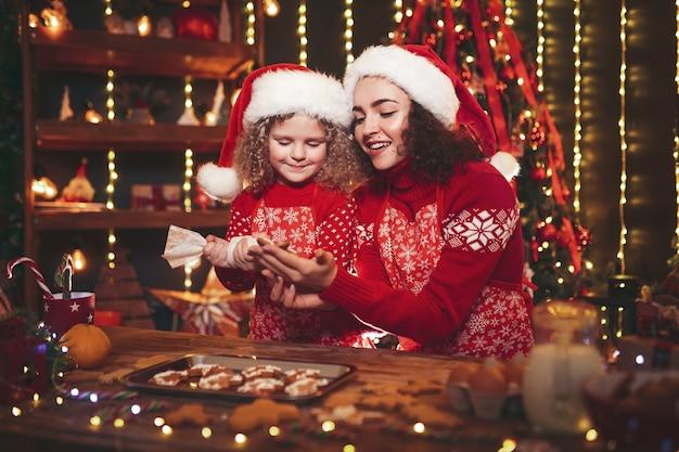 Prettige kerstdagen en prettige feestdagen. vrolijk schattig krullend meisje en haar oudere zus in santa hoeden koken kerstkoekjes.