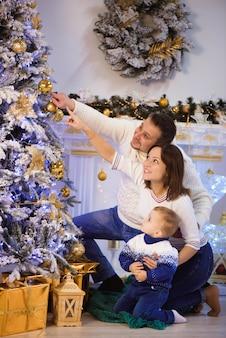Prettige kerstdagen en prettige feestdagen. vrolijke mama, papa en zoon die geschenken uitwisselen.
