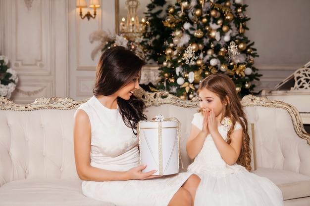 Prettige kerstdagen en prettige feestdagen. vrolijke moeder en haar schattige dochter meisje geschenken uitwisselen in witte klassieke interieur piano en een versierde kerstboom. nieuwjaar