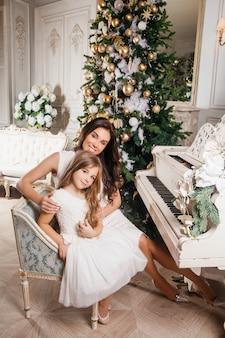 Prettige kerstdagen en prettige feestdagen. vrolijke moeder en haar schattige dochter meisje in witte klassieke interieur witte piano en een versierde kerstboom. nieuwjaar