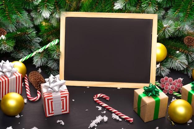 Prettige kerstdagen of gelukkig nieuwjaar frame samenstelling. spartakken, kerstmisspeelgoed, geschenkdoos, pluizige sneeuw, dennenappels, snoep en winterbessen op zwarte achtergrond. plat lag, kopieer ruimte voor uw tekst.