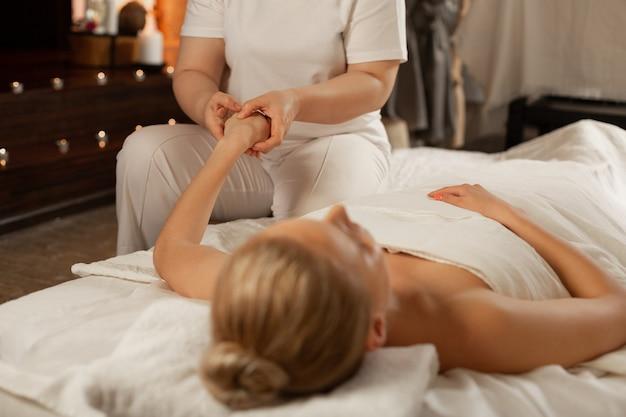 Prettige werkwijze. dame liggend op een ligbed bedekt met deken terwijl meester haar hand met speciale bewegingen verwerkt