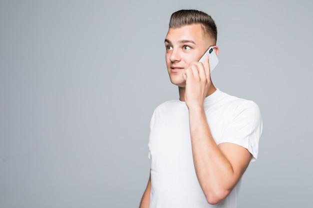 Pretty boy in wit t-shirt spreekt op zijn mobiele telefoon geïsoleerd op een witte muur