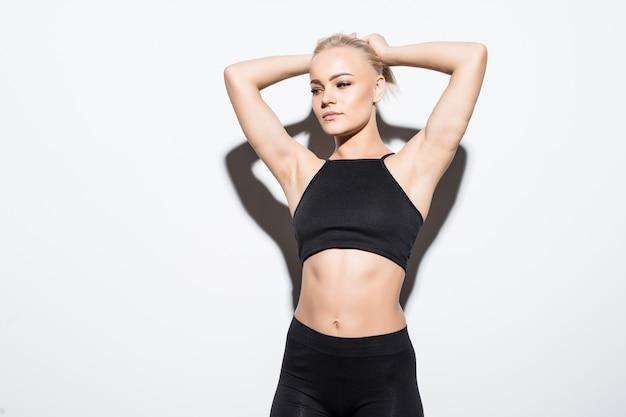 Pretty fitness meisje wordt moe en vermoeid voelen in de studio op wit gekleed in zwarte sportkleding