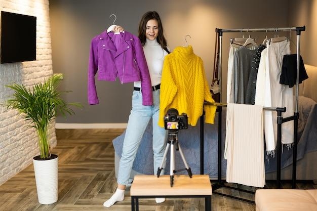 Pretty girl blogger influencer toont kleding voor volgers om het te verkopen via online streaming in de winkel