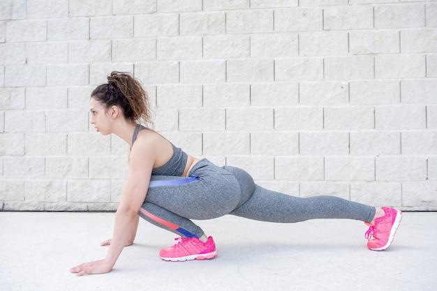 Pretty sporty woman stretching legs near brick wall