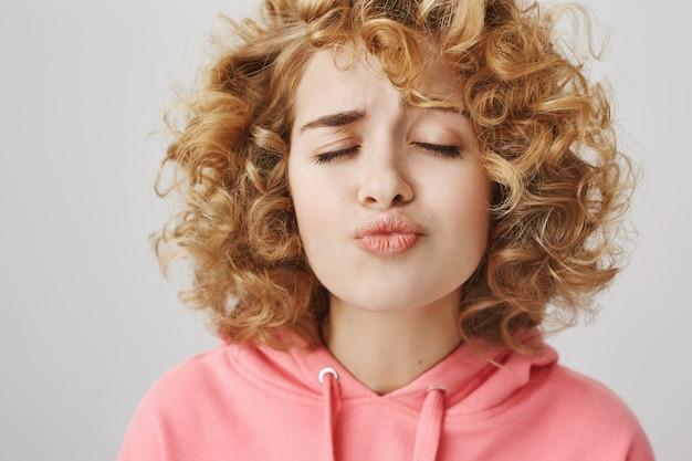 Pretty tienermeisje met krullend haar ogen sluiten en wachten op een kus