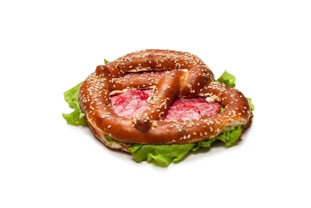 Pretzel met salami en sla geïsoleerd op een witte achtergrond. lekker hapje.