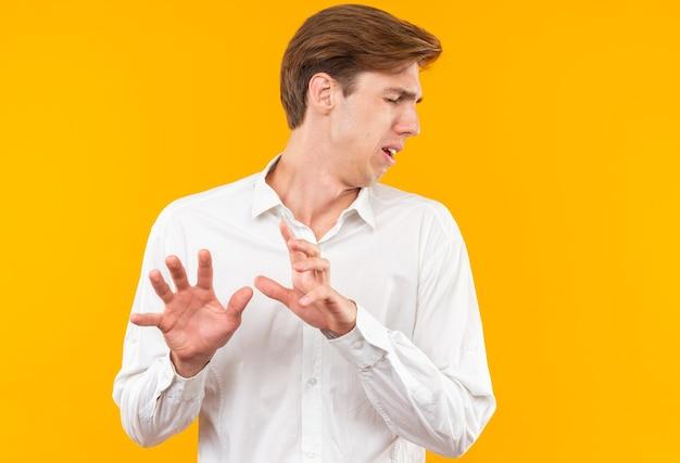 Preuts met gesloten ogen jonge knappe kerel die een wit overhemd draagt dat handen uitsteekt die op oranje muur worden geïsoleerd