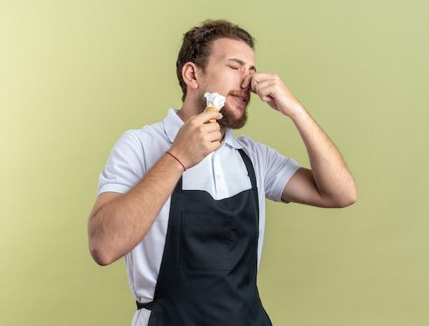 Preuts met gesloten ogen jonge mannelijke kapper dragen uniform aangebrachte scheerschuim met scheerkwast pakte neus geïsoleerd op olijfgroene achtergrond