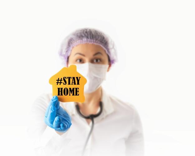 Preventie en stop coronavirus infectie concept. vrouwelijke arts of verpleegster in medisch beschermend masker dat verblijf thuis toont.