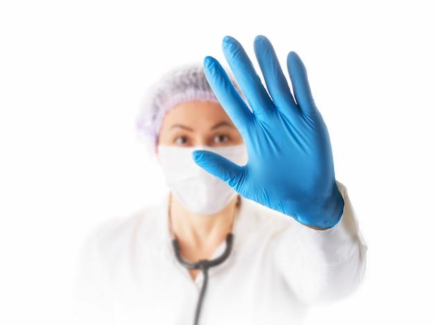 Preventie en stop infectie concept. stop coronavirus. vrouwelijke arts of verpleegster in medisch beschermend masker dat eindegebaar toont. focus op de hand.