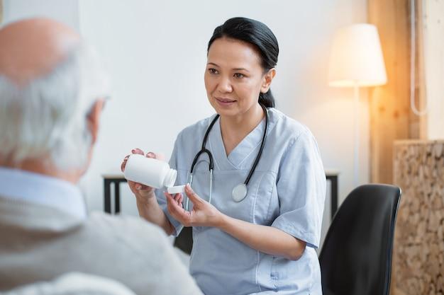 Preventieve maatregel. doordachte aziatische dokter stijgende fles gevuld met pillen terwijl staren naar senior man