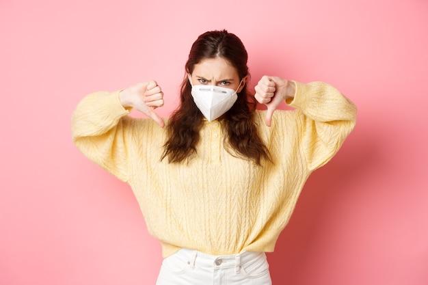 Preventieve maatregelen gezondheidszorg concept boze en teleurgestelde vrouw veroordeelt iets slechts met duimen naar beneden en fronsen een afkeer van het dragen van een medisch gasmasker tijdens covid
