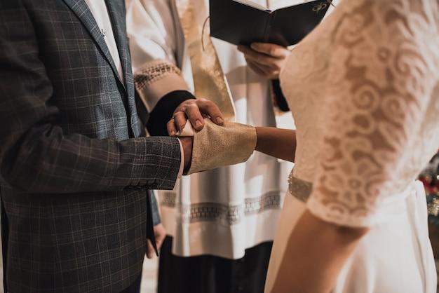 Priester bedekte de handen van de pasgetrouwden en zegende