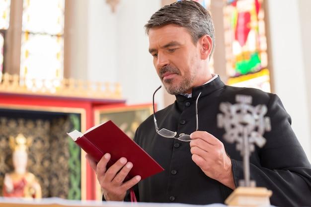 Priester die bijbel in kerk leest die bij altaar staat