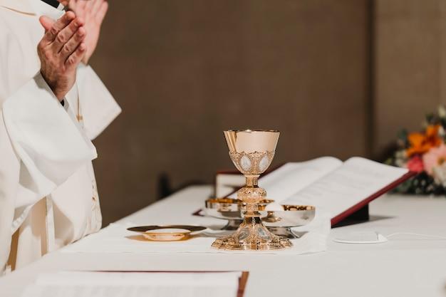 Priester die de drinkbeker houden tijdens een huwelijksceremonie huwelijkse massa. religie concept