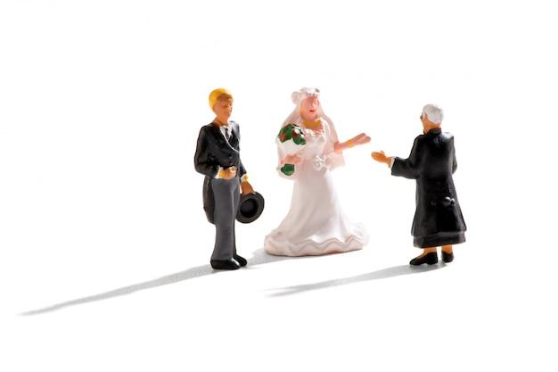 Priester die een miniatuurhuwelijksscène leidt