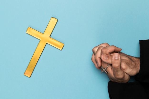 Priester die met houten kruis bidt