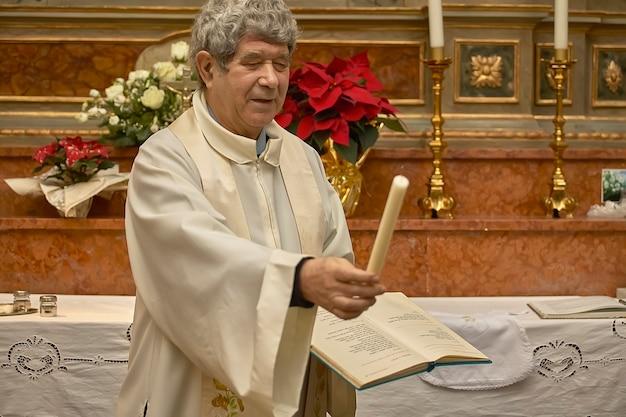 Priester geeft de kaars aan de doop, symbool van een deel van de christelijke ceremonie