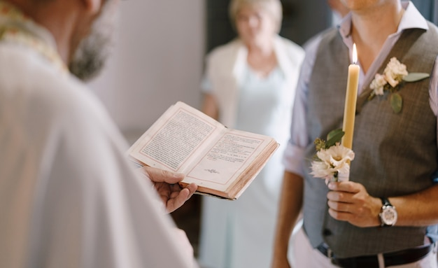 Priester met de bijbel staat naast de bruidegom met een kaars in zijn hand