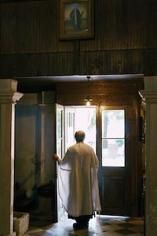 Priester opent de deuren van de kerk achteraanzicht