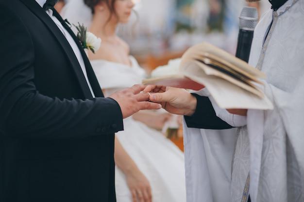 Priester zet de ring om de vinger van de bruidegom tijdens de orthodoxe huwelijksceremonie