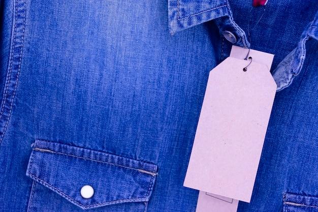 Prijskaartje op bruin shirt op jeans en close-up.