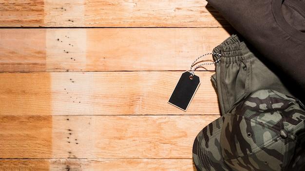 Prijskaartje op mannelijke kleding over het houten bureau