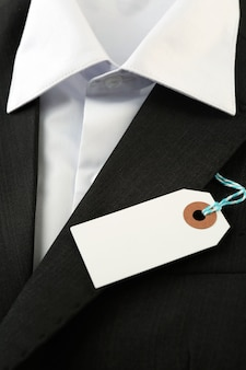 Prijskaartje op wit oppervlakoverhemd en zwarte jas, close-up