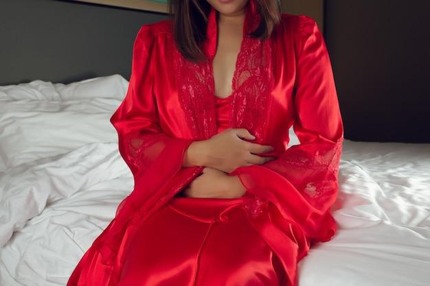 Prikkelbare darmsyndroom of ibs. aziatische vrouw in een zijden nachthemd en een rood gewaad die lijden aan menstruatiekrampen terwijl ze 's nachts op het bed in de slaapkamer zit. meisjes slapen niet vanwege buikpijn.