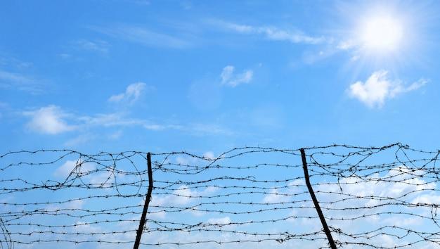 Prikkeldraad op blauwe hemelachtergrond, vrijheid, gevangenis en hoopconcept.