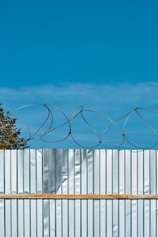 Prikkeldraad op een metalen hek tegen een blauwe hemel.