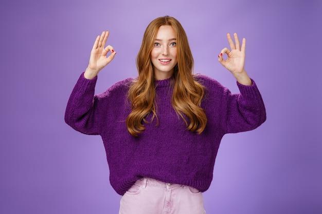 Prima daar ben ik het mee eens. portret van een vriendelijk en optimistisch jong 20s gembermeisje in paarse trui die handen opsteekt met oke of ok gebaar glimlachend in goedkeuring, cool product leuk vindend, aanbeveling gevend.