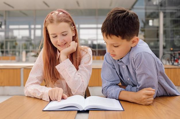 Primair secundair onderwijs, school, concept van vriendschap - twee studentenjongen en tienermeisje met rugzakken zitten, praten na school met boek en insect, foto