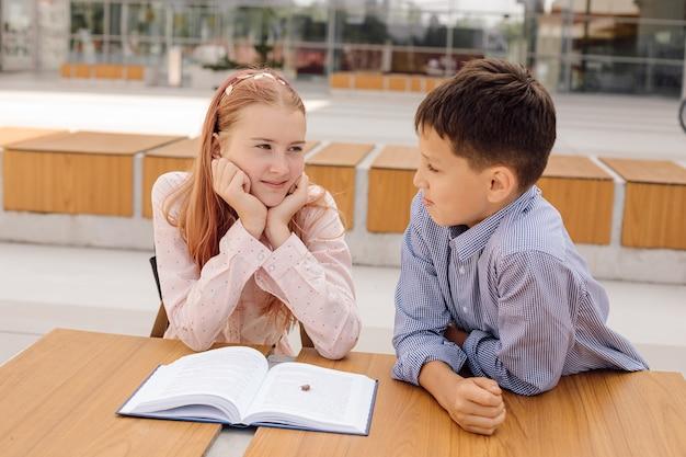 Primair secundair onderwijs, school, concept van vriendschap - twee studentenjongen en tienermeisje met rugzakken zitten, praten na school met boek en insect