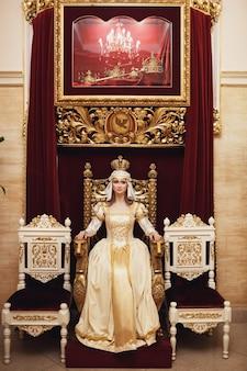Prinses in rijke gouden jurk zit voor de rode muur op de troon