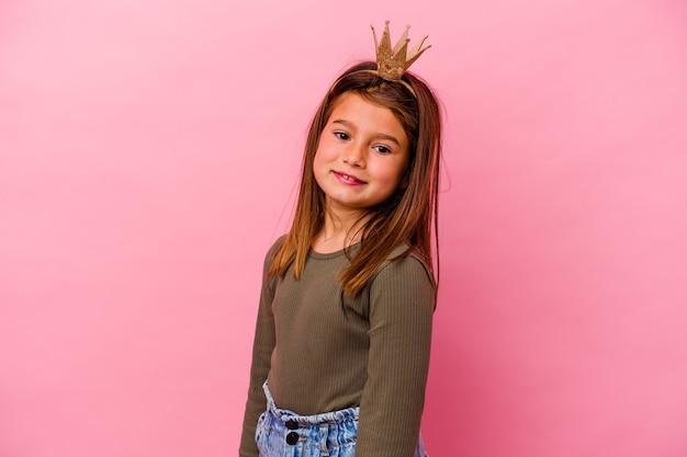 Prinses meisje met kroon geïsoleerd op roze achtergrond kijkt opzij glimlachend, vrolijk en aangenaam.