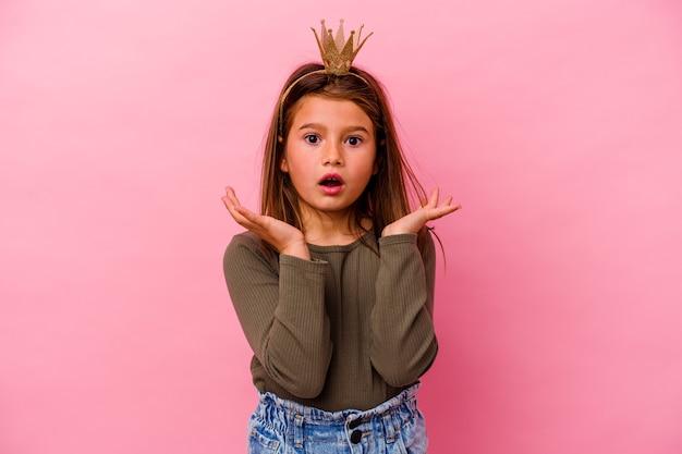Prinses meisje met kroon geïsoleerd op roze achtergrond verrast en geschokt.