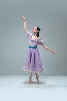 Prinses. mooie eigentijdse ballroomdanser die op grijze muur wordt geïsoleerd. sensuele professionele artiest die walz, tango, slowfox en quickstep danst. flexibel en gewichtloos.