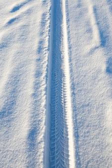 Print van de autoband op een met sneeuw bedekte weg