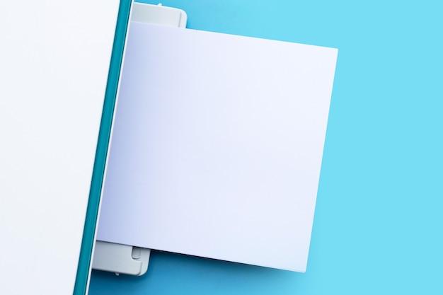 Printer en papier op blauwe achtergrond.