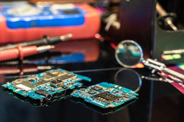 Printplaat met andere apparatuur op zwarte tafel ingenieur werkplek stockfoto
