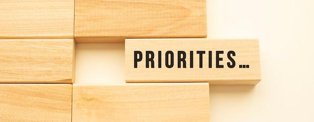 Prioriteiten tekst op een strook hout liggend op een witte tafel